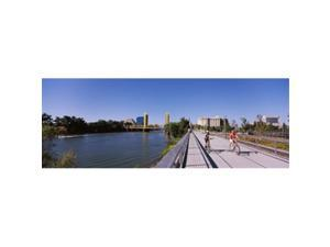 Panoramic Images PPI143559L Bicyclists along the Sacramento River with Tower Bridge in background  Sacramento  Sacramento County  California  USA Poster Print by Panoramic Images - 36 x 12