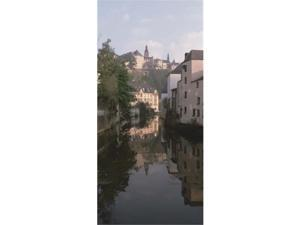 Panoramic Images PPI55057L Luxembourg  Luxembourg City  Alzette River Flowing through Grund District Poster Print by Panoramic Images - 12 x 36