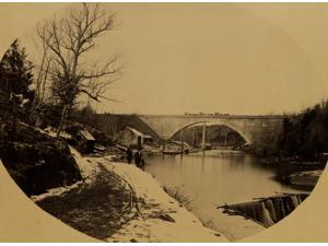 Two men standing near the Washington Aqueduct with the Cabin John Bridge in the background Poster Print (18 x 24)