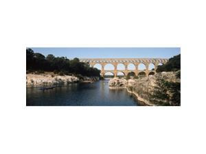 Panoramic Images PPI121701L Aqueduct across a river  Pont Du Gard  Nimes  Gard  Languedoc-Rousillon  France Poster Print by Panoramic Images - 36 x 12